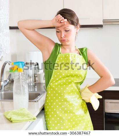 Sad girl cleaning furniture in kitchen at home