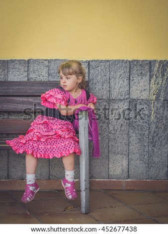 Sad girl dressed in pink dress sitting alone on a bench outside dance school - stock photo