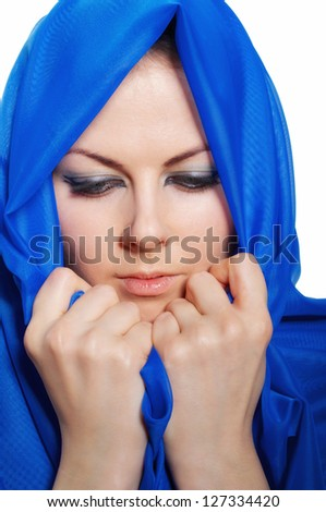 sad girl in blue hijab looks down isolated on white background - stock photo