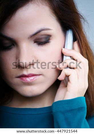 sad girl in blue shirt talking on the phone - stock photo