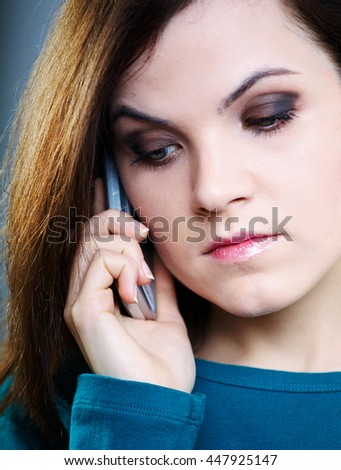 sad girl in blue shirt talking on the phone