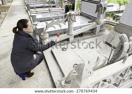 Sad girl in cemetery grave, religion - stock photo