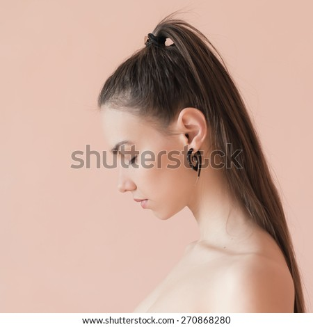 Sad girl in profile. Portrait of a beautiful brunette on a beige background. - stock photo