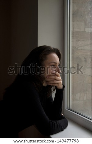 sad girl looking out the window - stock photo