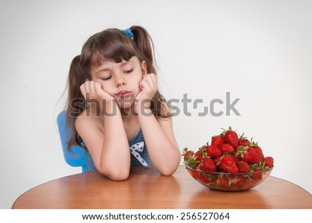 Sad girl looks at a plate of strawberries. Allergies to strawberries