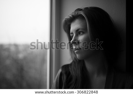 sad girl near window thinking about something