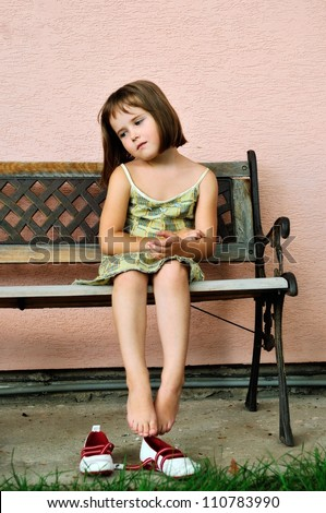 Sad girl - outdoor portrait of small cute child sitting on bench - stock photo