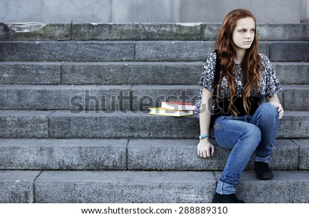 Sad girl sitting in the stairs - stock photo