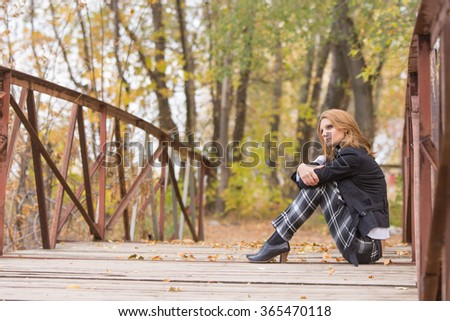 Sad girl sitting on a bridge in the forest