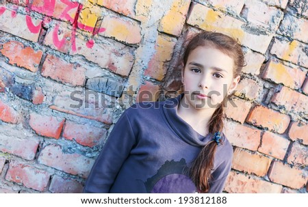 sad girl standing against a brick wall - stock photo