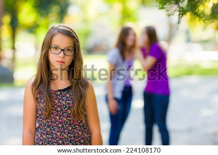 Sad girl standing in front of her evil girlfriends - stock photo