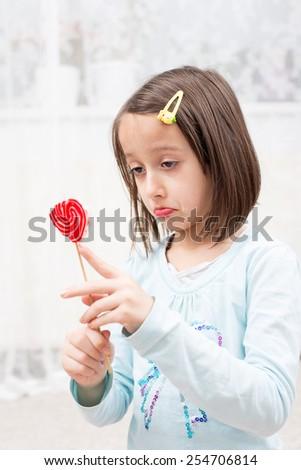 sad girl, who eating my lollipop - stock photo