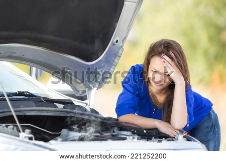 sad girl with a broken car with open hood - stock photo
