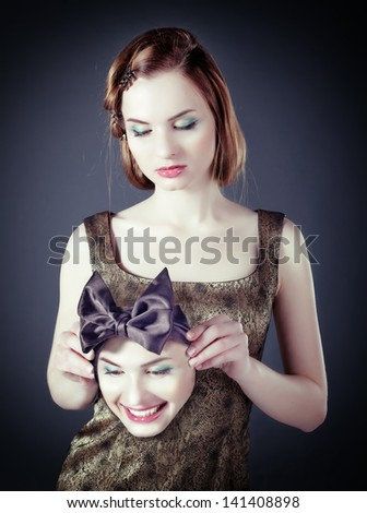 sad girl with a cheerful face mask (concept) - stock photo