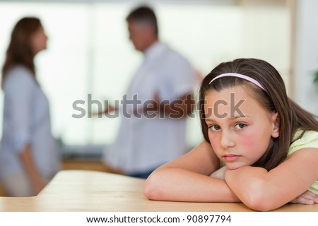 Sad girl with her fighting parents behind her - stock photo