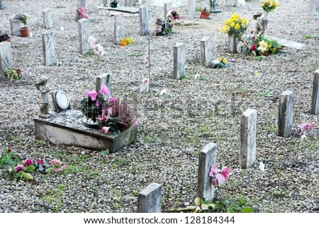sad grave of a young child died and other sad gravestones on small tombs - stock photo