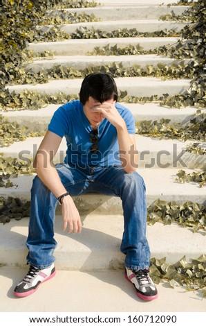 Sad guy  sitting on some park stairs thinking - stock photo