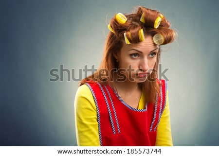Sad housewife with curlers on her hair - stock photo