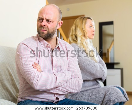 Sad husband sitting on a couch turned away from his wife after they had a quarrel - stock photo