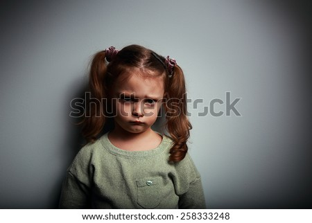 Sad kid girl looking with very unhappy face on dark background - stock photo