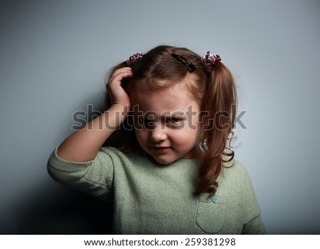 Sad kid girl with headache looking unhappy on dark background - stock photo