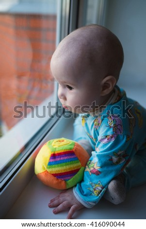 Sad kid looking at the window and want to get out - stock photo