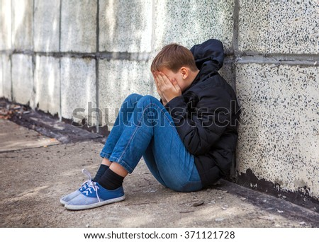 Sad Kid sit by the Wall on the Street
