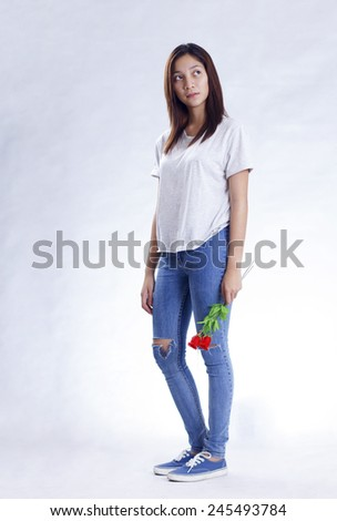 Sad lady in casual outfit standing in light gray background holding red roses. Valentines day concept. - stock photo