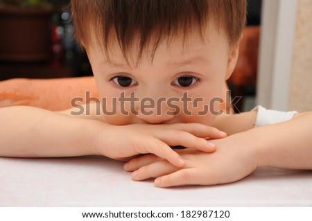 Sad litte boy looking down - stock photo