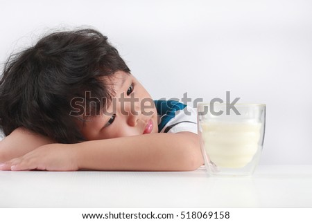 Sad little Asian boy refuses to drink milk