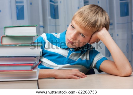Sad little boy at the desk with a stack of books