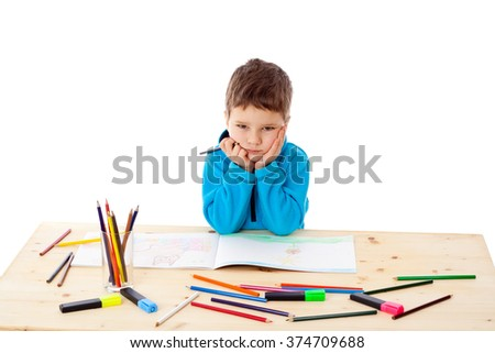 Sad little boy at the table draw with crayons, isolated on white - stock photo