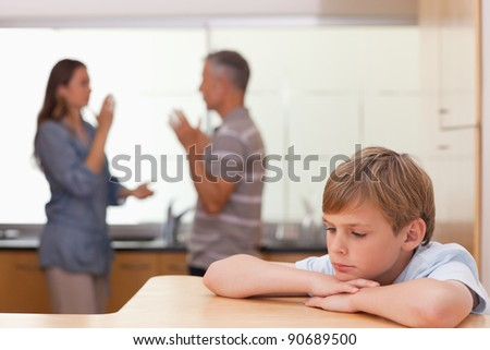 Sad little boy hearing his parents having am argument in a kitchen - stock photo