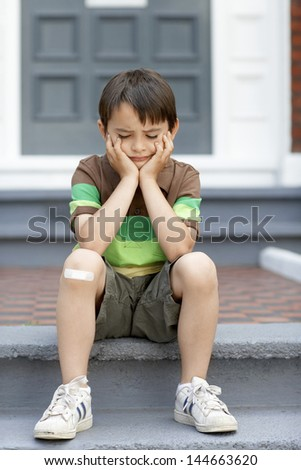 Sad little boy sitting on front steps of house - stock photo