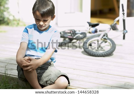 Sad little boy sitting on porch of house with bicycle in background - stock photo