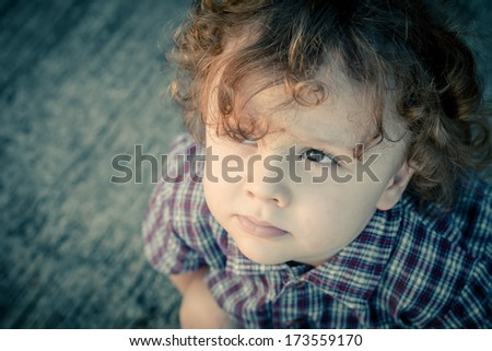 sad little boy sitting on the road - stock photo