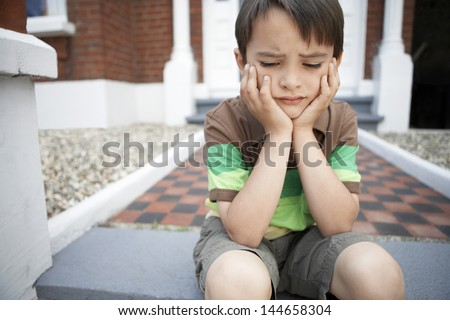 Sad little boy with hands on chin sitting on front steps of house - stock photo