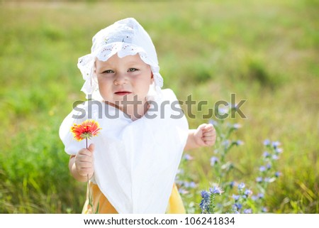 Sad little child with flower on green field