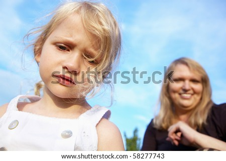 sad little girl and her mother on the background, outdoor - stock photo