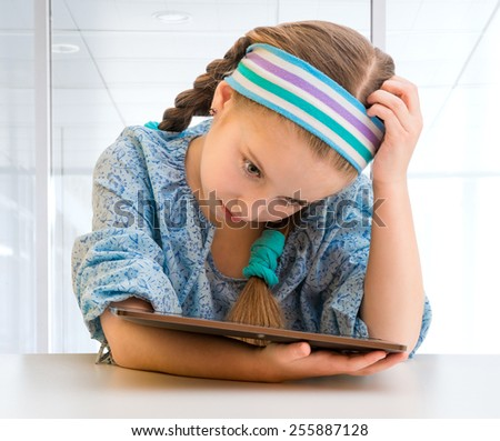 Sad little girl and her  tablet - stock photo