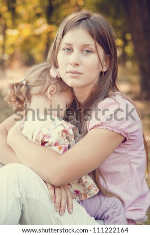 Sad little girl and mother in the park - stock photo