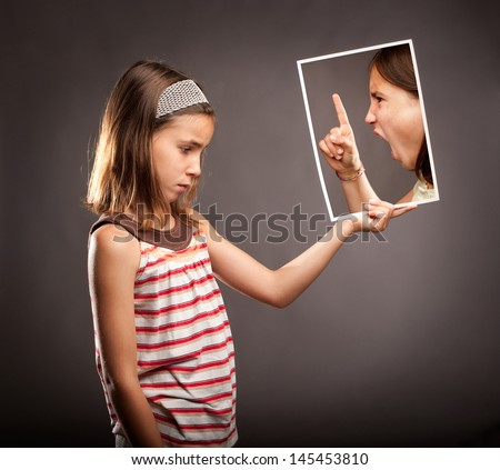 sad little girl  holding a portrait of an angry girl