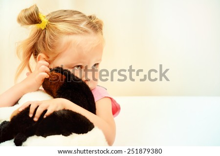 Sad little girl hugging her toy. - stock photo