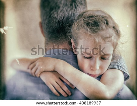 Sad little girl hugging his dad. Vintage effect.