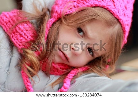 Sad little girl in a pink hat