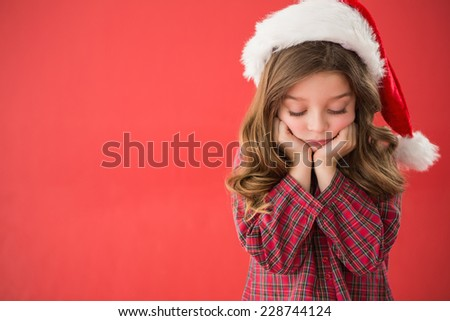 Sad little girl in santa hat on red background - stock photo