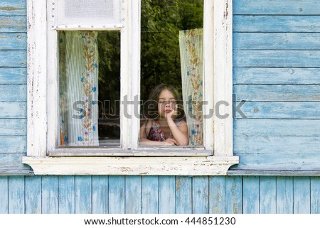 Sad little girl looking out the country house window leaning her face on her hand. Outside view - stock photo