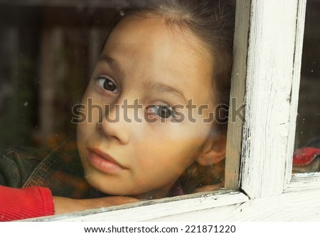 sad little girl looking through an old window - stock photo