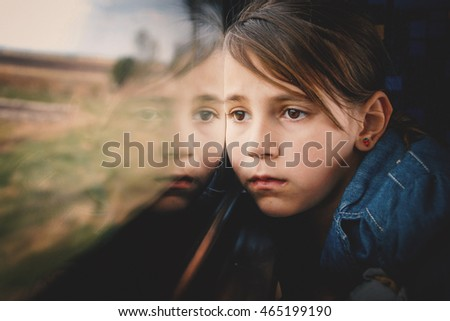 Sad little girl looking through window. She travels on a train.