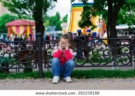 sad little girl near a playground, crying with his hands on face - stock photo